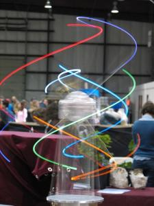 Snapshot of a Maker Faire project using multicolored swirls of light; people milling about in the background