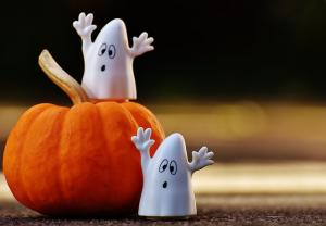 Two plastic ghosts on a pumpkin
