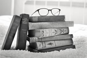 A pile of books with reading glasses on top
