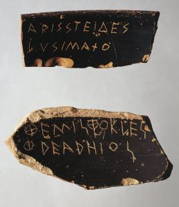 Two pottery shards used as ballots in ancient Greece; black background with clay-colored Greek letters