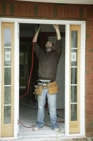Man in blue jeans working to fix a door jamb
