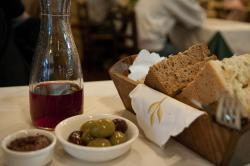 A bowl of olives, a carafe of red wine and a basket of rustic bread slices on a table with a cream-colored cloth