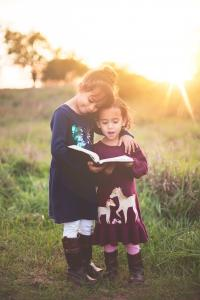 Two young girls standing and reading a book