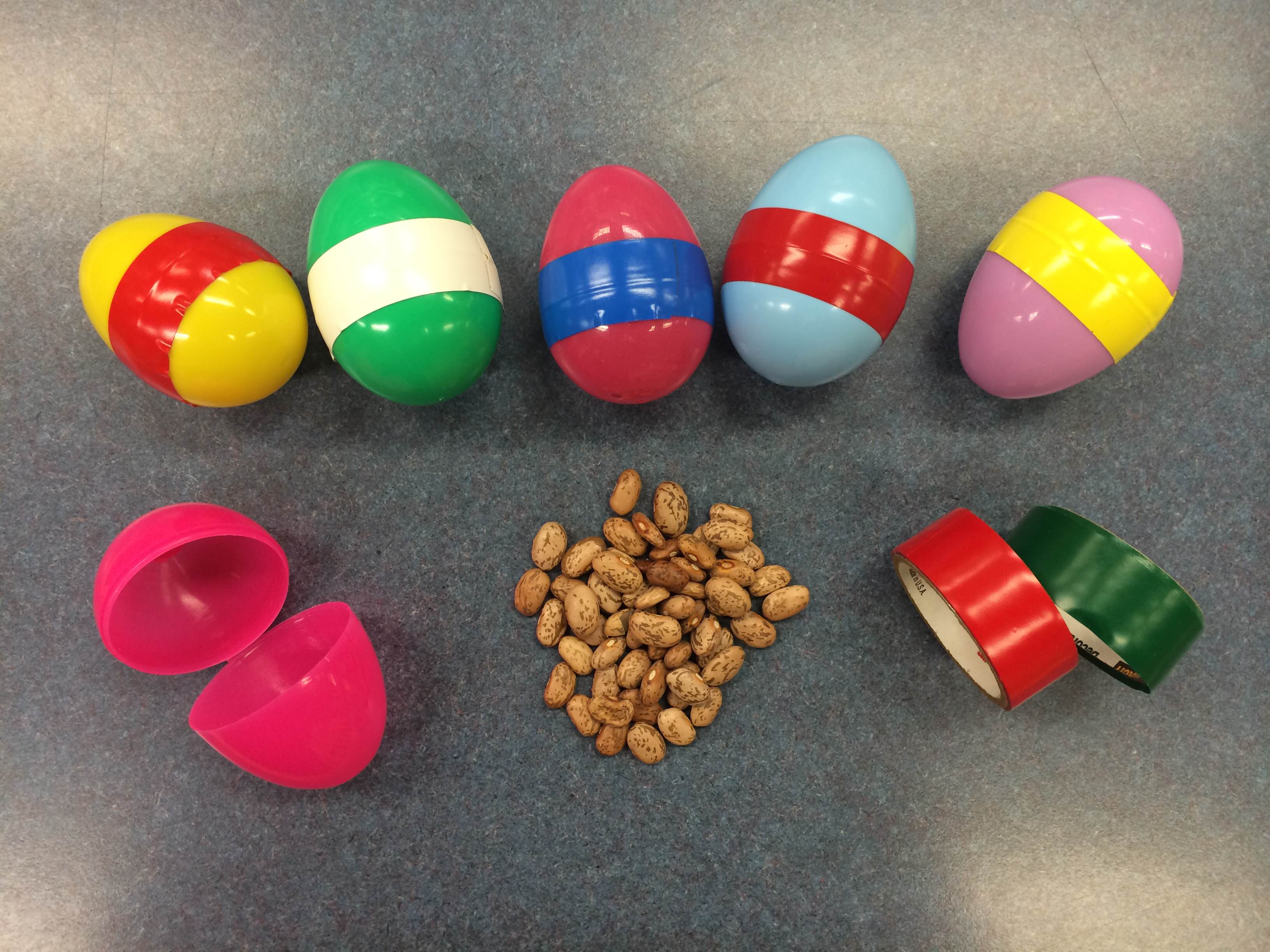 5 egg shakers with a plastic egg, beans, and 2 rolls of plastic tape