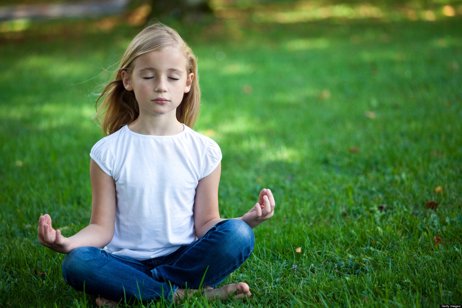 Child sitting cross-legged and meditating on a grassy lawn