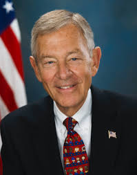Colro portrait of former Senator George Voinovich with edge of American Flag