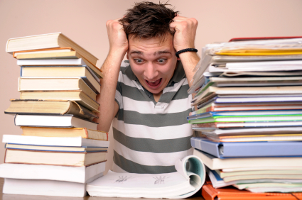 Young man stressed out between stacks of text books