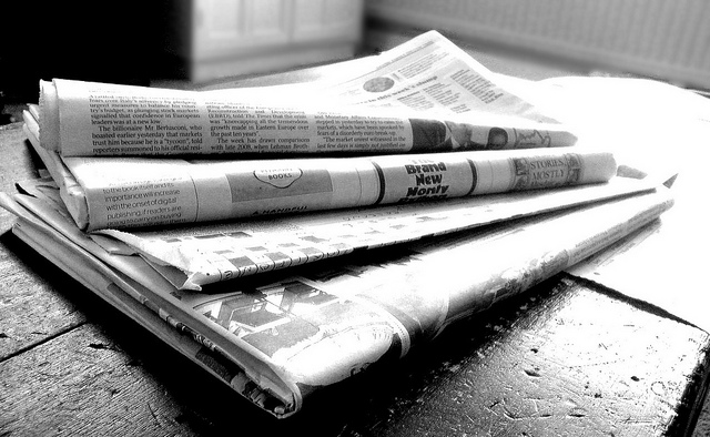 Black and white photo of four newspapers in a staggered stack. Photo by: https://www.flickr.com/photos/62693815@N03/